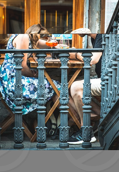 Young Couple Drinking At Outdoor Bar And Looking At Smartphone photo