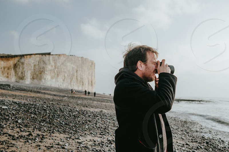 tourist guy walking around, taking picture and relaxing around  white cliffs   photo