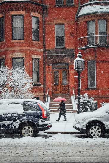 person in black winter coat walking beside black and white suv covering by snow near brown mansion photo