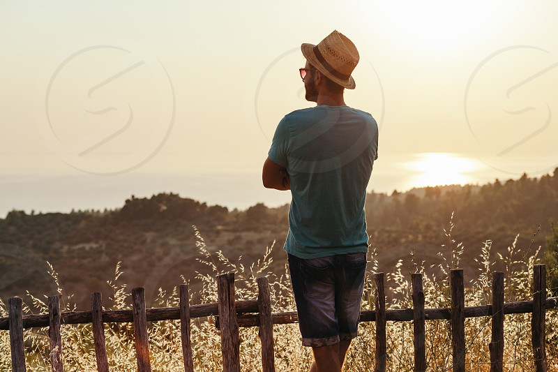 Young man enjoying sunset by the sea photo