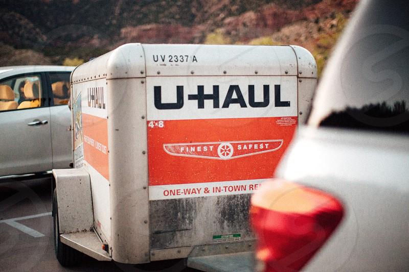uhaul white and orange box trailer on concrete road photo