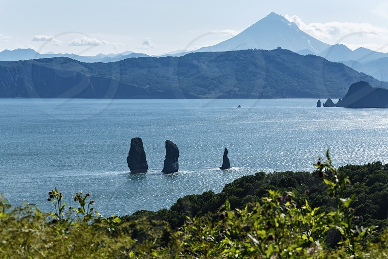 Beautiful summer landscape of Kamchatka Peninsula: Three Brothers Rocks in Avacha Bay (Pacific Ocean) and cone of Vilyuchinsky Volcano on other side of bay. Eurasia Russian Far East Kamchatka Region photo
