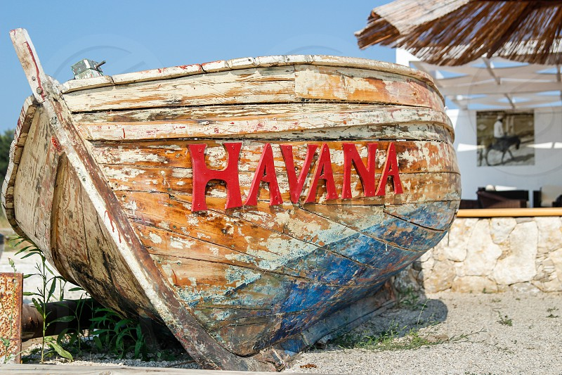 old battered boat on the beach with a sign on it saying Havana photo