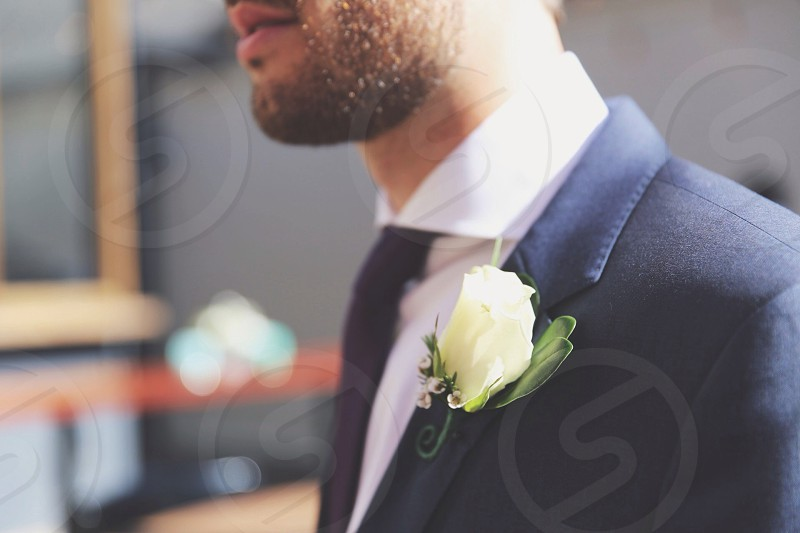 person wearing formal suit with white flower photo