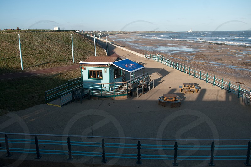 Cafe on the seafront at Whitley Bay. Promenade leads to St Mary's lighthouse photo