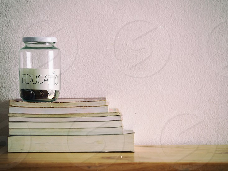 "book shelf and glass jars with coins and text ""EDUCATION"" saving money concept photo"