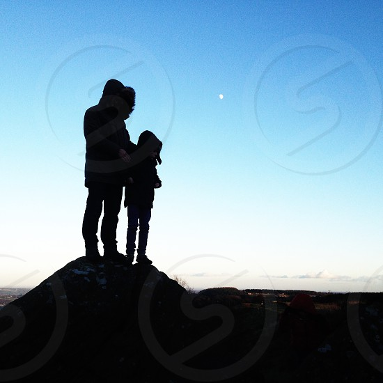 man and child on mountain top silhouette photo photo
