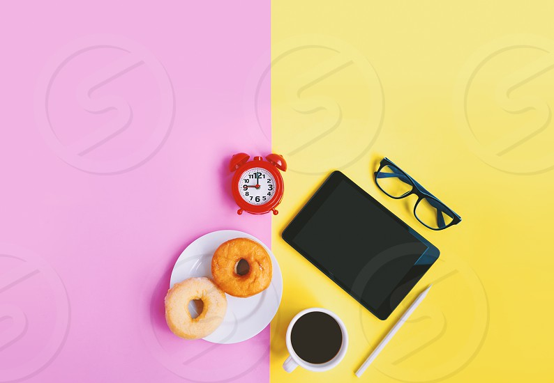 Modern home workplace Red alarm clock A cup of coffee donuts eyeglasses and tablet on yellow pink pastel background with copy space photo
