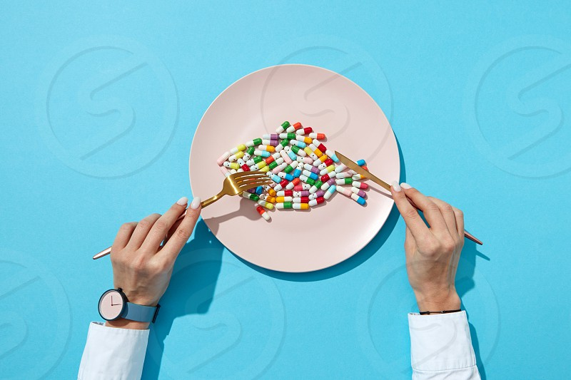 Fish from colorful pills and tablets on a white plate with girl's hands with watch on a blue background with shadows copy space. Top view. Colorful food supplement pills. photo