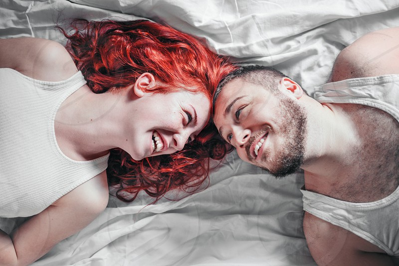Top view of a happy couple heads to each other on white bed sheets photo