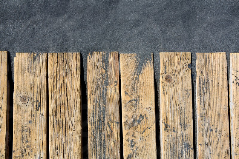 Black beach sand and wooden floor in volcanic Canary Islands photo