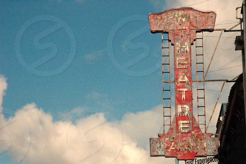 rusted theatre sign and cloudy sky photo