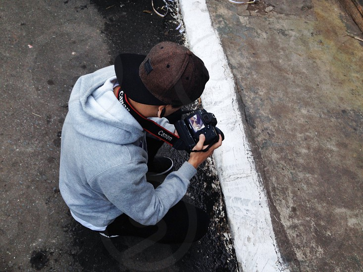 man in grey hoodie holding dslr camera photo