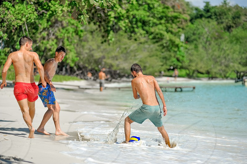 Friends playing football at the sunny tropical beach photo