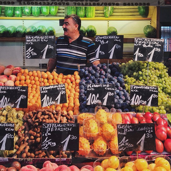 man in black white and blue striped polo shirt standing near fruits on display photo