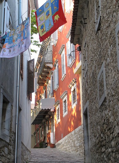 Narrow alley in Croatian old town; includes laundry sun speckled wall shutters. photo