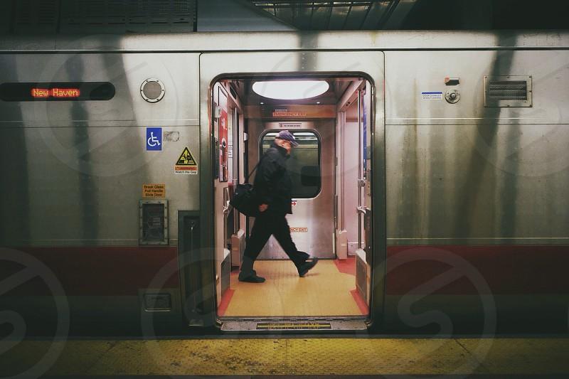 man walking pass through train door photo