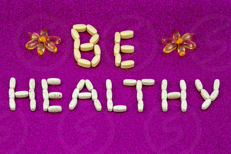 The inscription Be healthy created from pills and capsules with vitamins and dietary supplements on a pink monophonic background. Copy space. photo