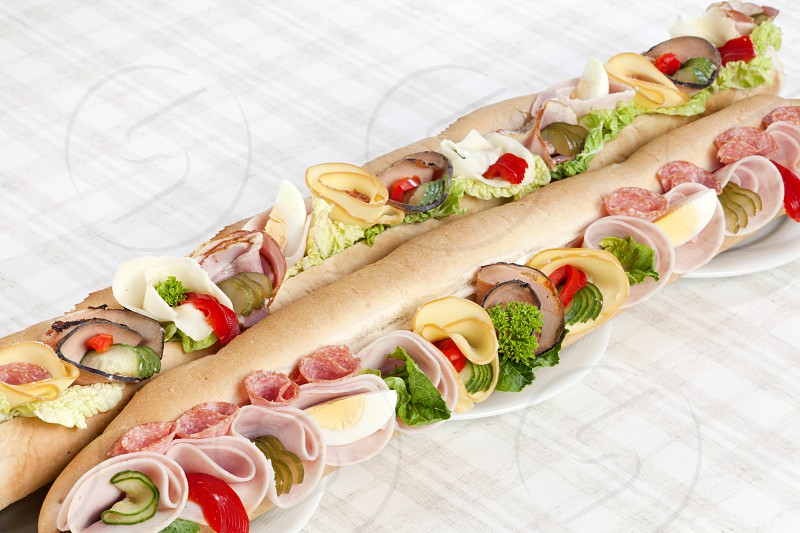 Long sandwich with ham salami eggs cheese pepper lettuce and cucumber on three plates. Selective focus photo
