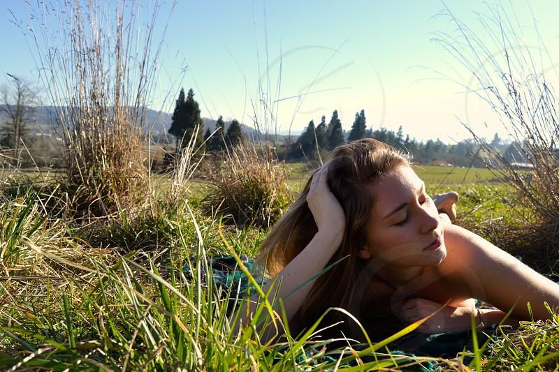 woman lying on green grass photo
