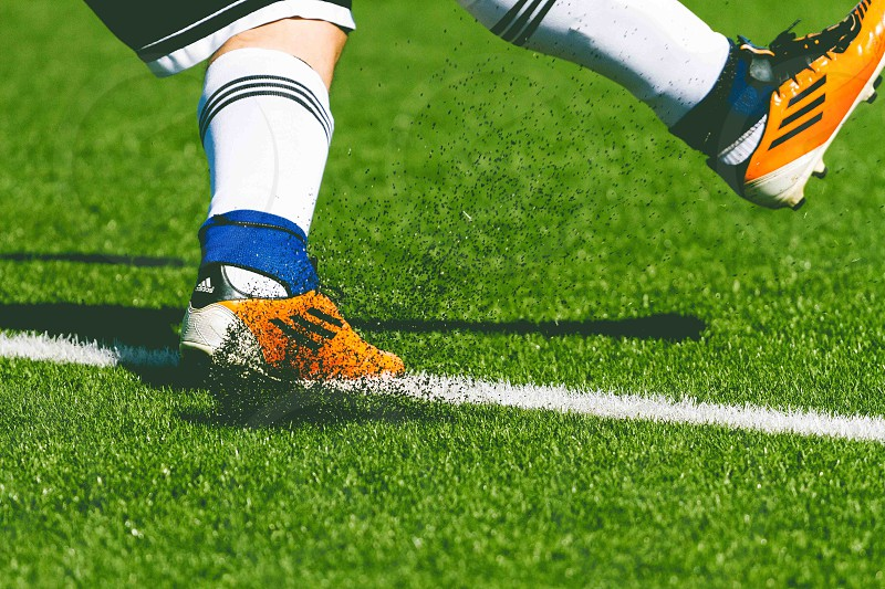 person wearing orange white and black adidas cleats and white black striped socks and white black shorts kicking on green short grass lawn with white line photo