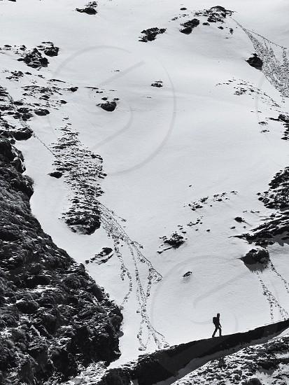 man walking on black mountain rock beside snow during daytime photo
