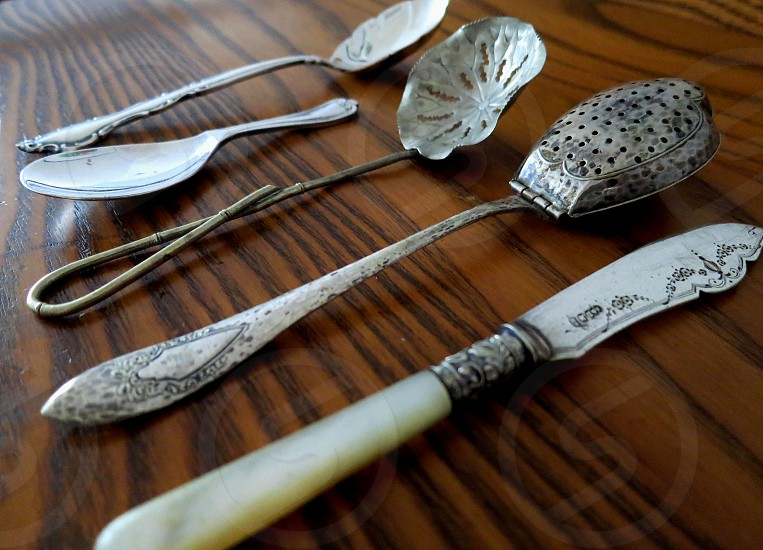 Antique spoons and knife on wooden table photo