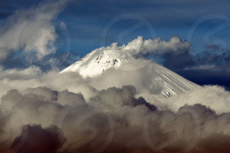 Volcanic landscape of Kamchatka Peninsula: top of cone of active Avacha Volcano fumaroles activity of volcano - steam and gas plume from crater clouds drifting across sky near volcano. photo