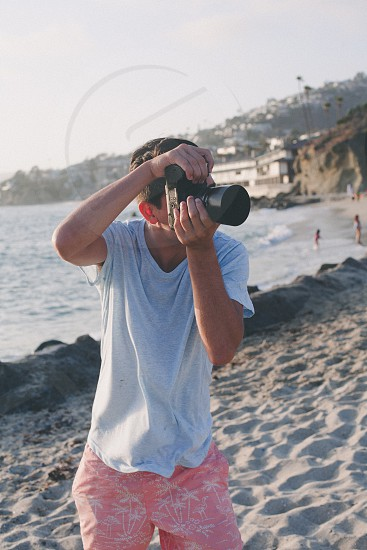 man at beach using a black dslr camera photo