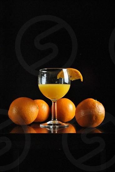 orange fruit and juice in wine glass photo