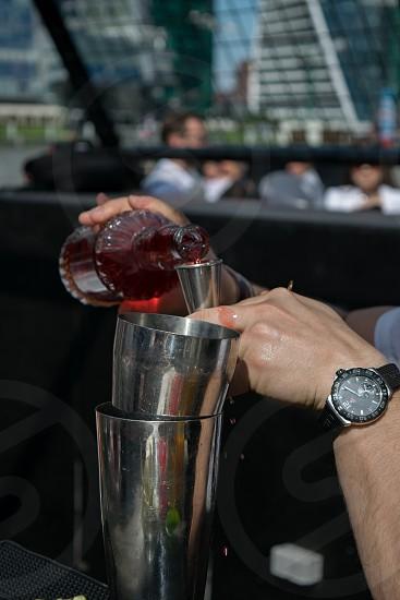 Close up of bartender hands pouring sweet juice into metal shaker photo