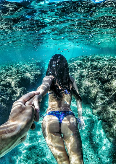 underwater photo of a woman in blue two-piece bikini holding man's hand photo