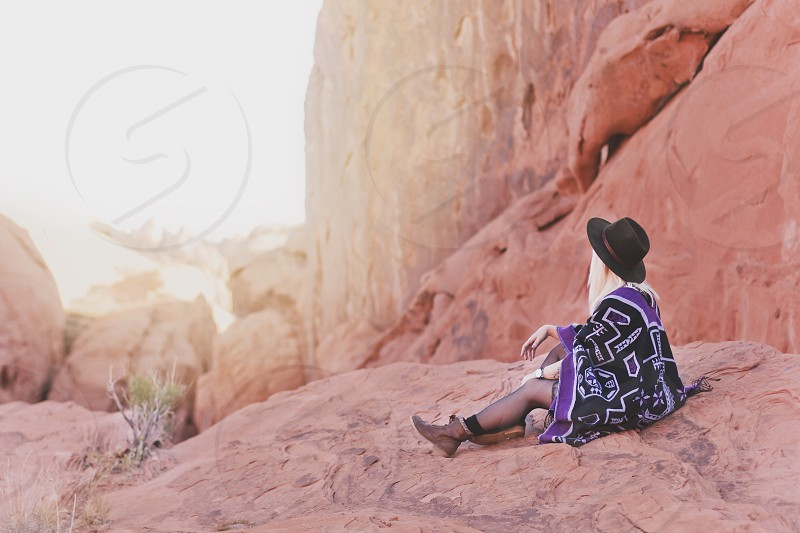 woman in purple and black cardigan wearing black hat and brown booties sitting on rock photo