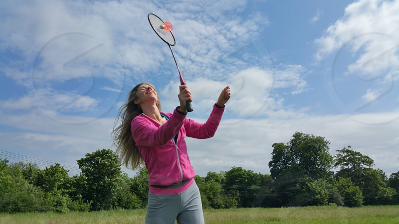 the funny blonde girl plays badminton photo