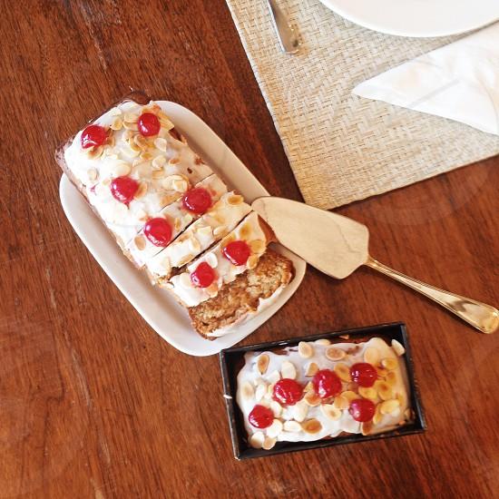 Buttermilk bread/cake with vanilla frosting & cherries. photo