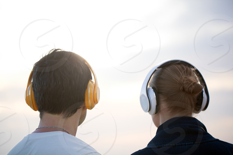 Back shot of man and woman listening to music in wireless headphones against evening cloudy sky background photo