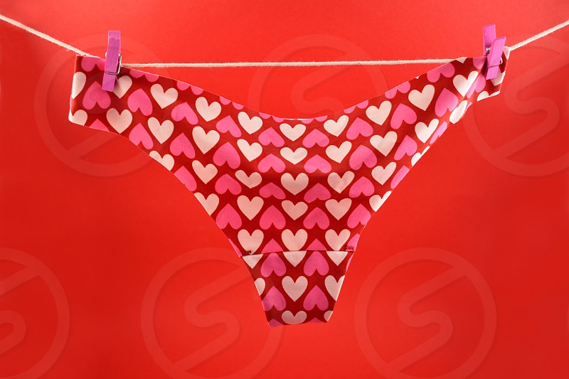 Pink panties with hearts. Valentines Day concept. Panties on a red background. Women's panties on the clothesline photo
