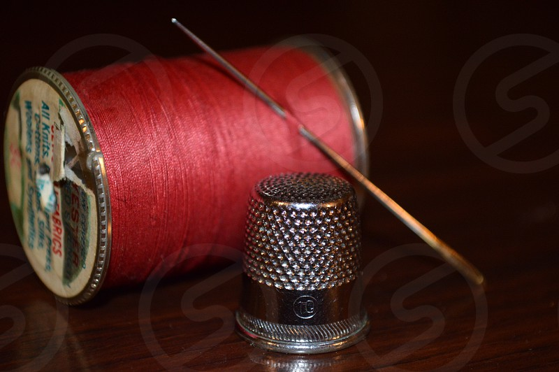 spool of red thread needle and silver thimble photo