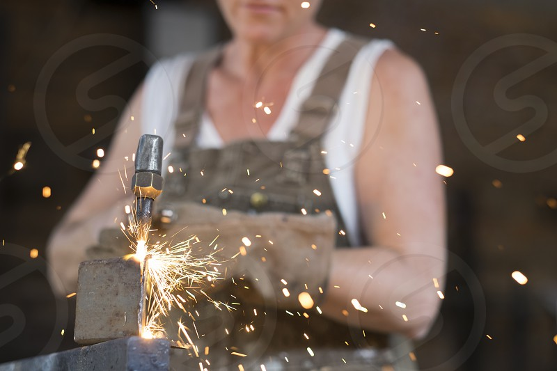 Female welder using welding torch in a metal shop. Sparks are flying. photo