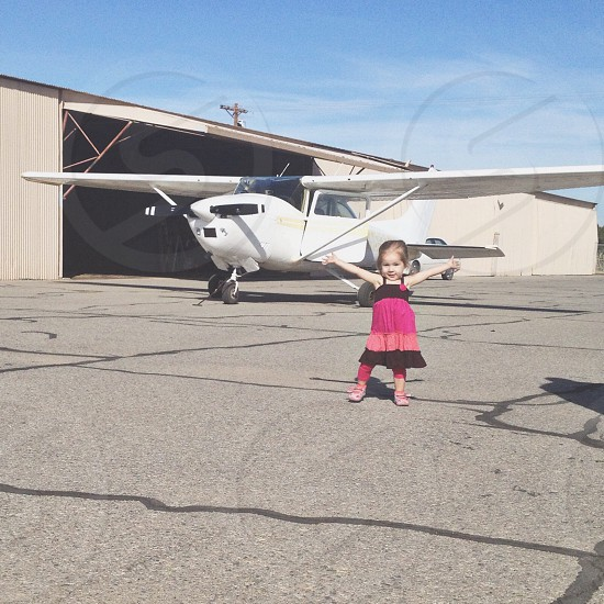 baby standing near the air plane photo