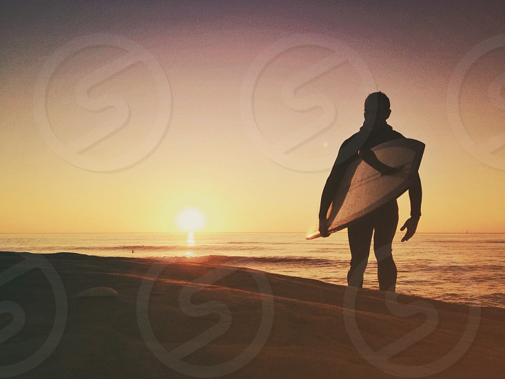 man holding surf board walking on bach photo