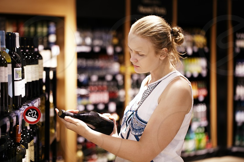 Woman shopping for wine or other alcohol in a bottle store standing in front of shelves full of bottles and holding bottle in her hand and reading inscription photo