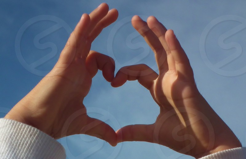 Love is the answer. Child's hands making a heart using the index fingers and the thumbs. Blue sky. photo