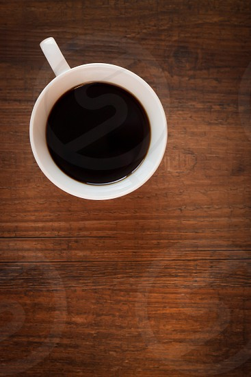 Cup of coffee on a woodgrain tabletop. photo