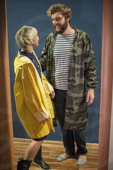 Happy smiling couple at home wearing waterproof capes photo
