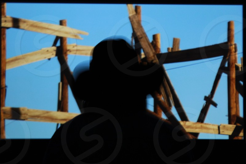 person wearing hat silhouette facing on wooden fence photo