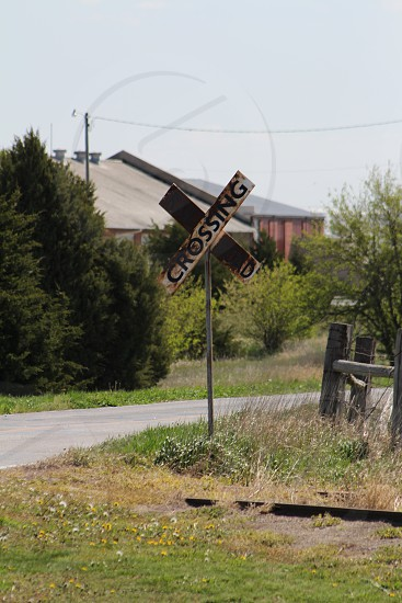 rail road crossing sign on street photo
