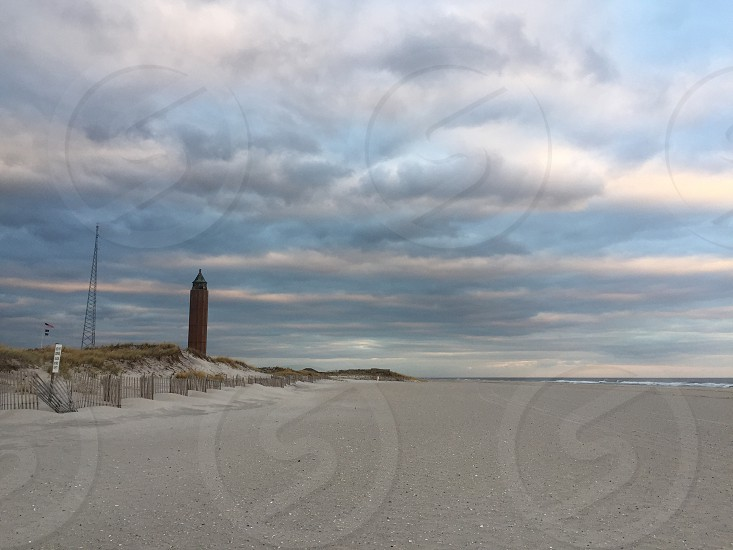 beach shore with brown concrete lighthouse under white cumulus clouds photo