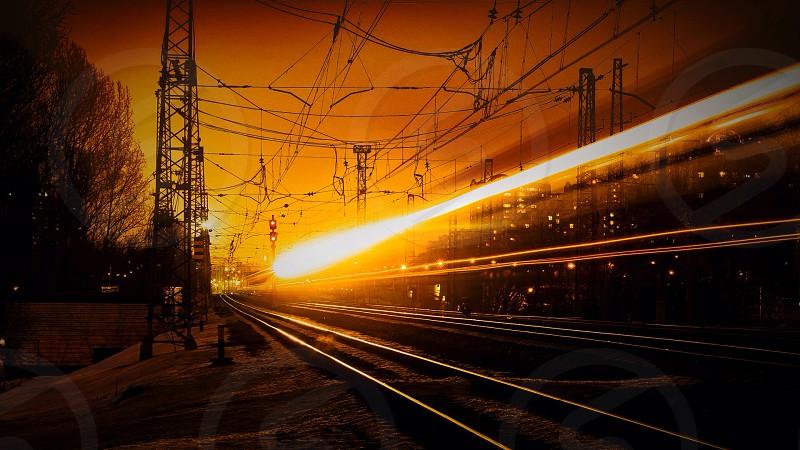 time lapse photo of yellow light passing railway photo
