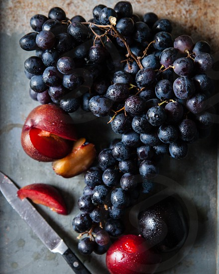 grapes on vine with plums and knife photo